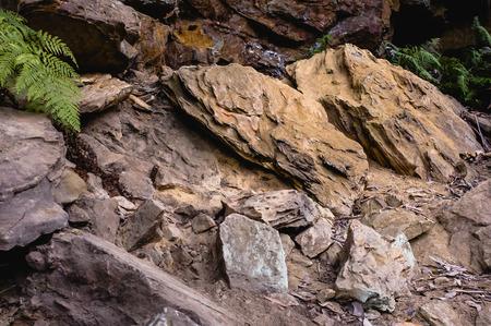 disorganization: Two symmetrical orange sandstone bolders near a darker rock in the Australian bush. Stock Photo