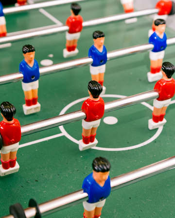 kicker: DSLR image of table football, table soccer, foosball, baby-foot or kicker players with red or blue shirts, white shorts and red socks suspended from a rotating bar around the centre circle on a green table with soccer line markings.