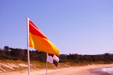 Beach flags on Australian beach. Red and yellow flag. Black and white flag. Lifesaver signs. Lifeguard flags on seashore at Coffs Harbour, Australia.