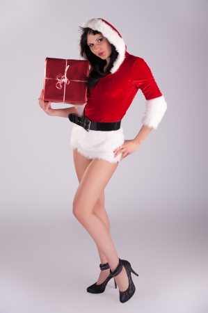 young beautiful Christmas woman, studio portrait Sexy Santa, grey background with long black hair and red hat Stock Photo