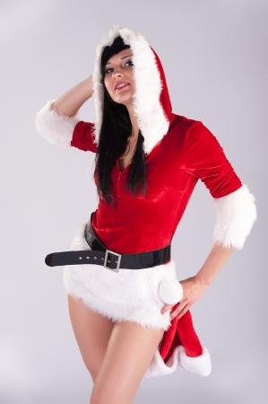 belle jeune femme de No�l, portrait en studio Sexy Santa, fond gris avec de longs cheveux noirs et rouges ha Banque d'images