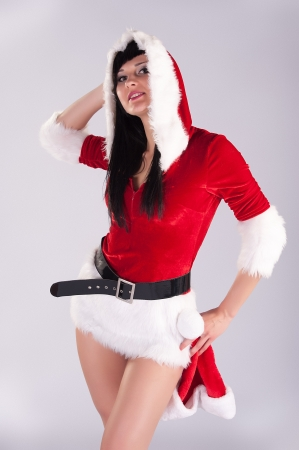 young beautiful Christmas woman, studio portrait Sexy Santa, grey background with long black hair and red ha
