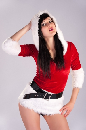 belle jeune femme de No�l, portrait en studio Santa sexy, fond gris avec de longs cheveux noirs et rouges ha Banque d'images