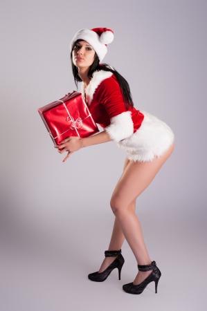 belle jeune femme de No�l, portrait en studio Sexy Santa, fond gris avec de longs cheveux noirs et un chapeau rouge