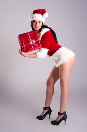 belle jeune femme de No�l, portrait en studio Santa sexy, fond gris avec de longs cheveux noirs et un chapeau rouge Banque d'images