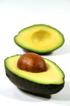 Avocado cut in half with seed in one half.