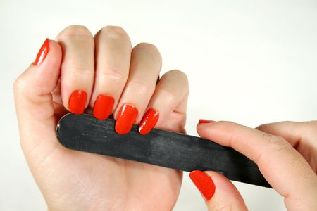 primp: Female filing her fingernails with an emery board.