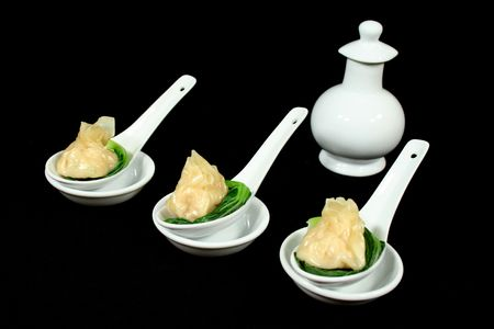 sums: Steamed dim sums with bok choy and soy sauce. Stock Photo