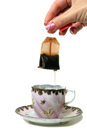 Dripping tea bag held above an antique teacup and saucer. photo