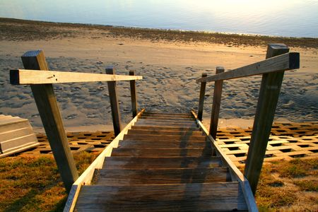 hand rails: Old wooden stairs leading to the beach at daybreak.