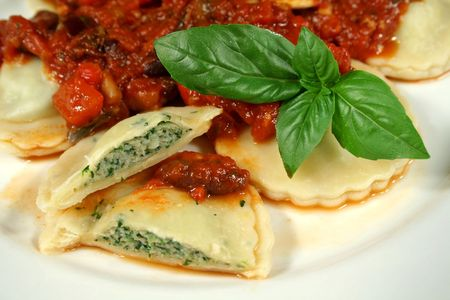 Delightful chicken and spinach ravioli with capsicum, olive and tomato sauce. Stock Photo