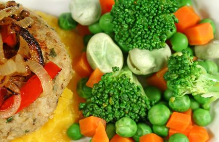 Chicken patty and fried onion with fresh steamed vegetables. photo