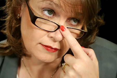 Tight shot of businesswoman with finger on glasses. Stock Photo
