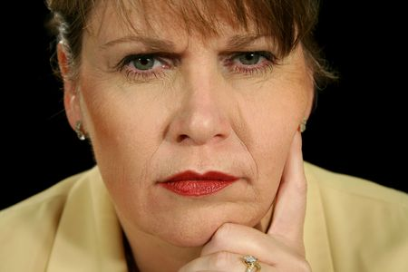 incensed: Mature businesswoman with a stern and angry look.