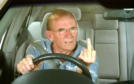 Middle aged man gives rude sign in road rage incident. photo