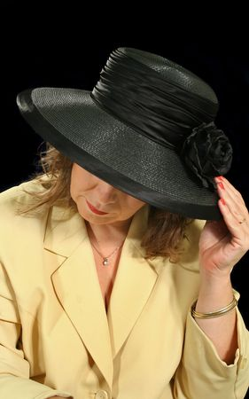downhearted: Middle aged woman underneath a black hat.