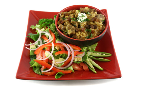 sultanas: Indian lamb biryani with sultanas and yoghurt and a side salad. Stock Photo