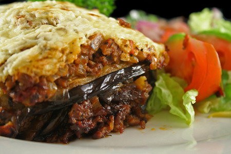 Lamb moussaka with egg plant cheese and salad. Stock Photo
