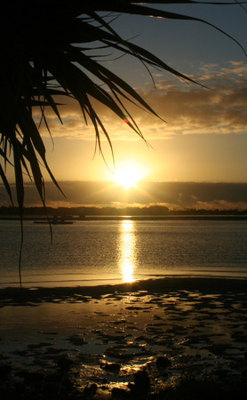Sunrise reflected in water by the beach. Stock Photo - 1446883