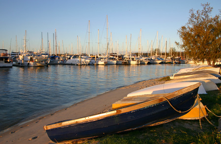 dinghies: Dinghies on the beach with yachts and cruisers. Stock Photo