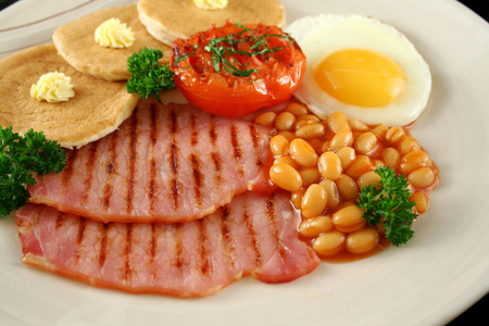 baked beans: Breakfast of grilled bacon, tomato, egg, baked beans and pancakes.