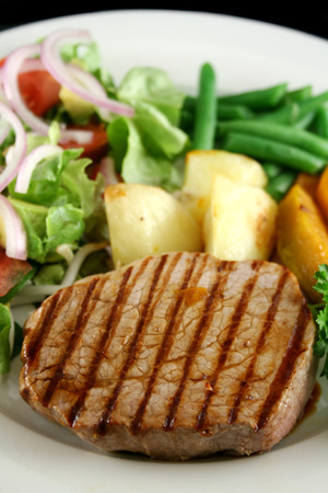 unprocessed: Hearty dinner of steak, vegetables and a side salad.