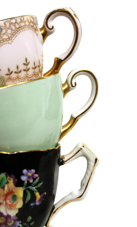 plated: Three antique teacups stacked with gold plated handles.  Stock Photo