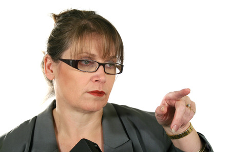 gesticulating: Serieous middle aged businesswoman gesticulating and pointing. Stock Photo