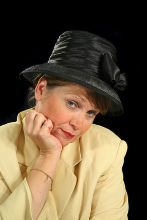 enquiring: Middle aged female with an inquiring look in a black hat.