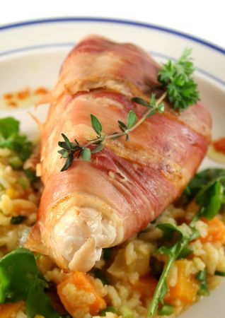 prosciutto: Chicken wrapped in prosciutto on pumpkin and risotto. Stock Photo