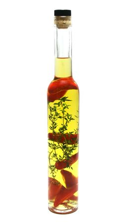Red chillies and thyme preserved in a bottle of olive oil. Stock Photo