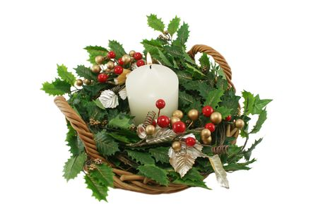 Candle burning in a Christmas basket arrangement.
