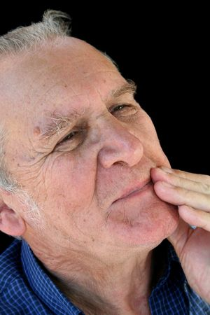 implausible: Cautious senior man with hand to mouth. Stock Photo