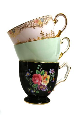 Three colorful antique teacups in a stack.
