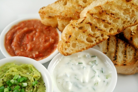 Delicious and colorful trio of dips with grilled Turkish bread. photo