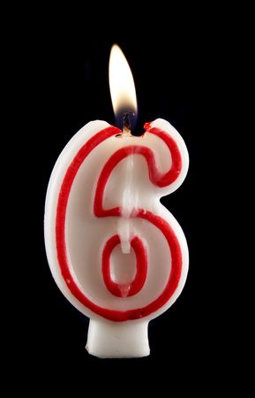 number six: Burning number six candle with dripping wax. Stock Photo