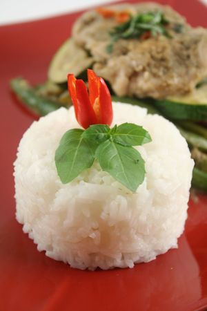 poached: Delicious chili rice stack with Thai green poached chicken with green beans and zucchini. Stock Photo