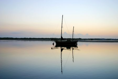 ketch: Old vintage ketch moored in a lagoon just before dawn. Stock Photo