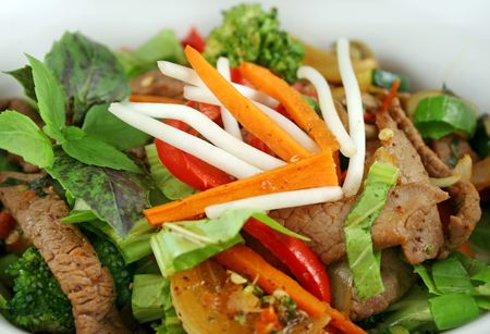 vegtables: Stirfry beef and vegtables with a purple green basil garnish.