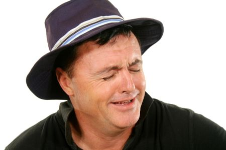 perturbed: Middle aged man in a hat bursts into tears.