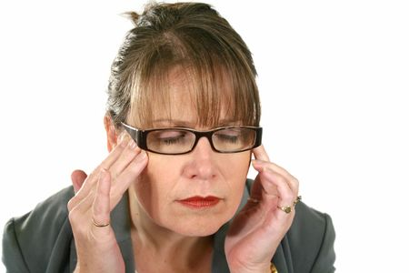 bothered: Middle aged businesswoman with hands to forehead with a headache. Stock Photo