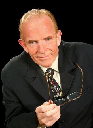 smug: Middle aged businessman looking smug and holding glasses.