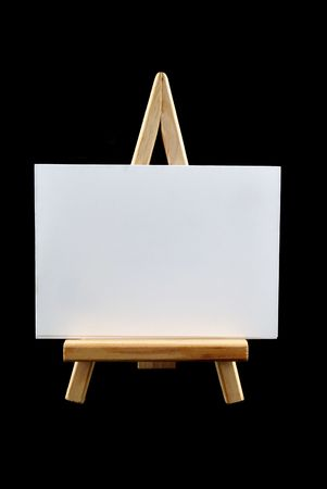 Wooden easel with blank white board on black. Stock Photo