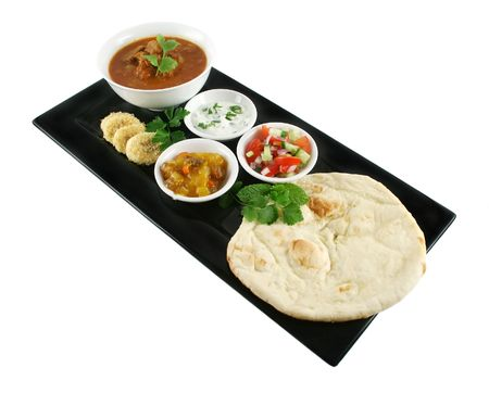 naan: Indian feast of vindaloo curry, naan bread, mango chutney, banana and coconut, tomato and cucumber. Stock Photo