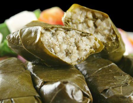 wijnbladeren: Griekse dolmades omwikkeld met wijnbladeren met rijst en salade. Stockfoto