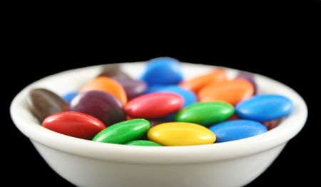 fatter: Assorted crunchy and colorful chocolate buttons in profile