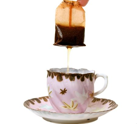 Dripping tea bag in an antique tea cup. Stock Photo