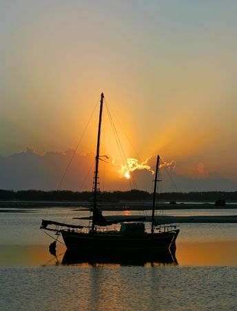 ketch: Daybreak through clouds over an old ketch.