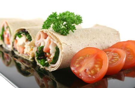 Mixed platter of delicious ham and chicken salad wraps.