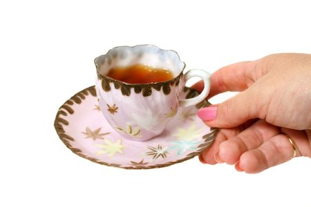 Tea in an antique tea cup served by hand. photo